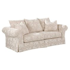 Showcasing off-white upholstery, rolled arms, and a tailored skirt, this understated sofa offers a neutral anchor for colorful pillows and decor.