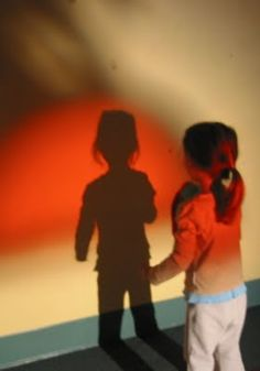 Child and shadow in front of wall with color projection from an overhead projector.