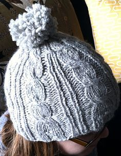 During a marathon of the TV show Bones I noticed Temperance wearing two cute hats. I liked the cabled pattern of one and the large pompom on the other, so I decided to combine those two elements in one hat -- a quick knit with bulky yarn!