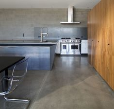 The downstairs communal living spaces flow freely between kitchen, dining room, and living room. Concrete block walls and polished concrete floors emphasize the heavy materiality that supports the visual lightness of the upper story.