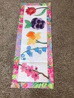 This is a Patchwork runner with all the blocks made in the 5x7 6x10 8x12 hoop. This is a machine embroidery design. There are 5 different blocks in this table runner and they are then joined with the sewing machine. There is a daffodil, a tulip, cherry blossoms, a pansy and lily of the valley. The quilting shown in the photos is done in the hoop. The full pattern for the table runner is included. You could make anything you like for eg a bag, placemat quilt, sewing machine cover etc.
