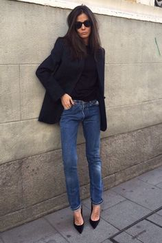 A black blazer is worn with a black top and jeans