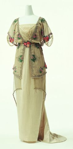 "1910-1911 Evening Dress by Paul Poiret: silk satin dress with silk tulle overdress, embroidery of beads and metallic thread, tulle peplum. ""...In 1906, when the S-curve silhouette was still overwhelmingly popular, Poiret introduced high waist corsetless dresses. He shifted the fashion trend substantially from 19th-century dresses in artistic forms with excessive decoration toward innovative clothing that accentuated the natural beauty of the human body..."" 