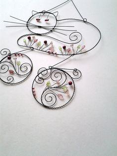 Kočičí - závěs Drátovaná dekorace z černého vázacího drátu, dozdobená skleněnými korálky, kytičkami a lístečky a voskovanými skleněnými kuličkami v barvě růžové,vínové a zelené. Vhodné k zavěšení na zeď, dveře, skříň, nad kočičí pelíšek.... Kočička s fousky :20 cm a 13 cm, průměr koleček cca 9 a 7 cm,celý závěs cca 40 cm