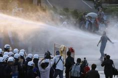 """Police use a water cannon to disperse a demonstrator during a protest against a trade pact with mainland China, near Taiwan""""s government headquarters in Taipei, March 24, 2014.  REUTERS/Edward Lau"""