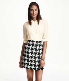 Short, gently flared skirt in a cotton blend with a visible zip at back. Unlined.