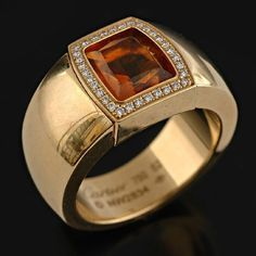 A citrine and diamond ring by Cartier the wide band centrally set with a fancy cut citrine surrounded by a border of round brilliant cut diamonds, all in 18ct gold.