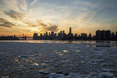 Nog een dag dichter bij de lente: De zon achter de skyline van Manhattan als ijs drijft naar beneden de East River in New York als ontdooien ijs en draaglijker temperaturen bracht vreugde aan miljoenen op woensdag