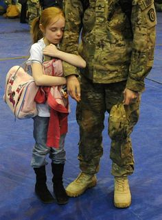 Alyssa Smith hugging the arm of her father after his return from Afghanistan. <3