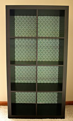 Adding fabric backing to an IKEA Expedit Bookcase. Could do this with wallpaper. Laura Ashley has some nice options. Add decorative wood to top and, possibly, legs.