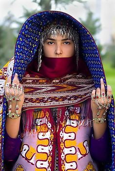 Turkmen Bride In Turkmenistan, the traditional wedding ceremony sees the bride dressed up in a red dress made from silk homemade fabric studded with silver or gilded pendants.