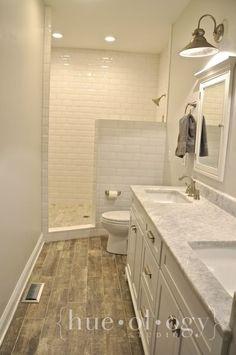 Metro wall tiles, interlocking vinyl wood flooring and Carrara Marble vanity surface, all available at SOLID