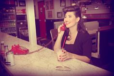 Retro red phone with cord at Plouffe's Cup 'N Saucer Diner while wearing a black pencil dress, bolero, and birdcage  |  Photographer:  LAURIE BRANDT of LAURIE BRANDT PHOTOGRAPHY www.lauriebrandt.zenfolio.com  |  Makeup:  JESSICA PULEO of COSMIC MAKEUP www.cosmicmakeup.com  |  Hair:  CASSANDRA FALCONE HAIR ARTIST www.cf-hair.com