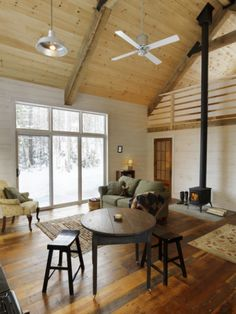 Great room features large windows, high ceiling, and paneled walls