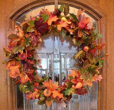 Front door with beautiful fall wreath in orange colors
