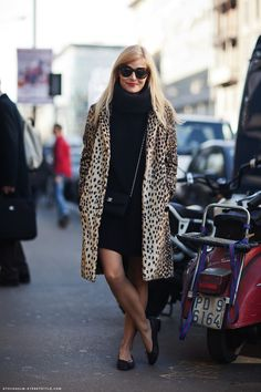 Instant Outfit: All black oversize turtleneck with black mini skirt, chain-strap Chanel bag, simple black flats, and a leopard print coat.