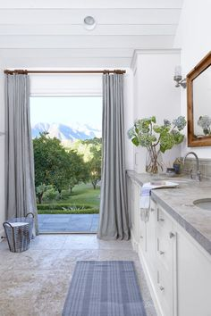 Maya looked no further than the Topatopa Mountains for inspiration in the master bathroom. The earthy limestone floor  is embedded with fossilized rocks and shells. Hand embroidered linen draperies in a soft shade of sand add polish without distracting from the stunning scenery.