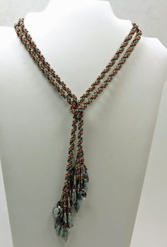This spiral rope lariat necklace is extremely versatile. It can be worn in various ways to give a new look each time. The photos only show a few of the ways it can be worn. It can even be tied and worn as a belt. Its been beaded using Japanese glass seed beads in one of my favorite color combinations...dark copper, bright copper, and turquoise. The bright and dark copper beads spiral around a core of turquoise seed beads. A beautiful fringe made with Czech pressed glass seafoam daggers and…