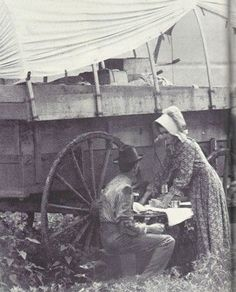 A pioneer family taking a meal at their covered wagon on their way to Colorado and beyond via wagon train. The women dressed simply wearing cotton and calico dresses and bonnets to stay as comfortable as possible.