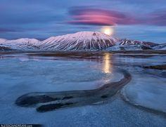 All sizes | Pink Moonrise, via Flickr.  イタリア・マルケ州のシビッリーニ山脈国立公園で撮影された美しい写真。日没後間もないため、山の上にかかる多重の笠雲が夕焼けによって赤紫色になっている。その背後から月が昇り始めている。さらに山の前面には半分凍った湖が広がっている。  https://twitter.com/ogugeo/status/301089765049106432