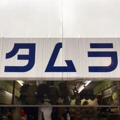 タムラ帽子店。シンプルでスタンダードな文字ではあるが「タ」と「ラ」のはらいがグイッとのびてる部分で韻を踏んでいることがわかる。「ム」のような三角形の文字が真ん中あることで対称性も出ていて魅力的だ。