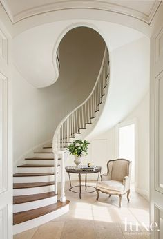A sinuous spiral staircase graces the entry of a traditional plantation style home.