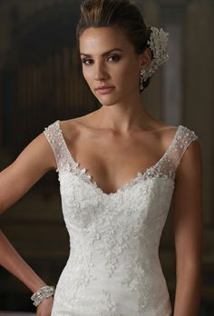 David Tutera for Moncheri. Love the lace on this dress, not a huge fan of the straps though.