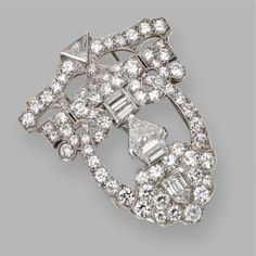 DIAMOND CLIP-BROOCH, CIRCA 1925 Of modified open work shield shape, set with baguette, bullet-cut, trapeze-cut, triangular-shaped, calf's-head-cut and old European-cut diamonds weighing a total of approximately 4.25 carats, mounted in platinum.