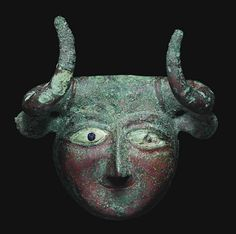A SUMERIAN COPPER PROTOME   EARLY DYNASTIC III, CIRCA 2550-2250 B.C.   In the form of a bull-man, cast with thick walls, the oval face with raised arching brows above lidded almond-shaped eyes, the sclerae inlaid in white stone with lapis lazuli pupils, the long triangular nose with lightly-grooved nostrils, his thin mouth smiling, with projecting triangular ears and large forward-curving tapering horns, the poll outlined by a raised ridge  4 in. (10.1 cm.) wide