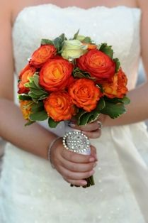 Orange and ivory rose bridal bouquet with a satin and diamond handle treatment and a diamond buckle. Bridal bouquet from Seasonal Celebrations. http://www.seasonalcelebrations.com