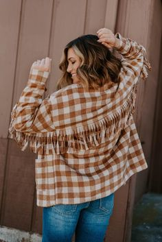 Walk out of the house in some country charm and style with the Zanna jacket! It features a checker boxy fit, fringe tassel detail on the sleeves and back, and a button-down closure. All you need is a great pair of denim and a cute top to complete this look! #noragrayboutique #shopnoragray #onlineboutiques #boutiquefinds #boutiqueclothing #instastyle #styleinspiration #fallstyles #midweststyle #indianaboutique #midwestboutique #fallfashion #boutiquejackets #falljackets #womensjackets #shakets