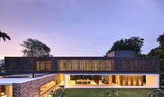 ONG & ONG kap house is defined by its stone and timber facades, blue pools and waterways, and lush garden greenery.