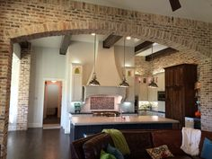 Brick archway. Cupboards. Kitchen layout. Microwave and appliance garage. Seperate fridge and drink center. Pantry behind range and two entrances and swinging doors and a work space (they put coffee maker in there )