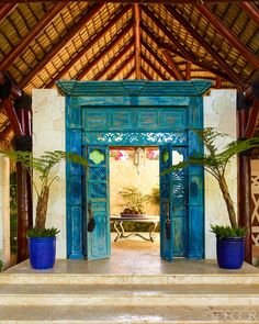 Now, family and friends make their way up a wide set of steps fashioned from local coralina stone and are ushered through a pair of enormous 19th-century wood doors sporting their original weathered turquoise finish. Montoya bought the doors in Colombia more than a decade ago, knowing that someday he would build a home where they belonged. From there, a winding stone path leads to a series of cottages, most of which have lower levels that are open to the tropical air. There is a luxurious…