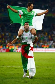 Abdelmoumene Djabou of Algeria celebrates on the shoulders of teammate Essaid Belkalem after a 1-1 draw with Russia