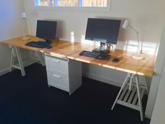 Long home office desk made from two IKEA Gerton beech table tops, with support from two IKEA Adils legs and Finnvard trestles, as well as cut down Brimnes drawers.
