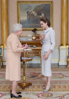 U.S actress Angelina Jolie, right, is presented with the Insignia of an Honorary Dame Grand Cross of... - AP Photo/Anthony Devlin, pool