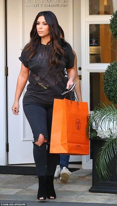 Low key look: Kim wore a faded N.W.A. Tshirt and ripped jeans as she left a cosmetic dermatologist in Beverly Hills on Thursday