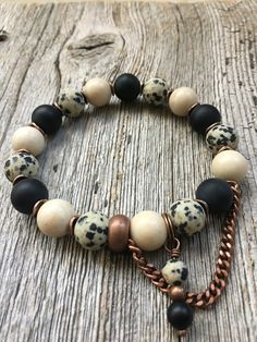"""W481 Whimsy A combination of frosted black Agate, Riverstone and matte Dalmatian Jasper, with copper accents and an off center chain and beaded dangle to add some """"whimsy"""" to the design."""