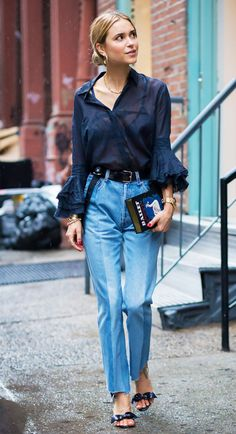 Pernille Teisbaek wears a button-down shirt with ruffle sleeves, high-waisted paneled jeans, sandals with bow-detailing, gold jewelry, and an Olympia Le-Tan book clutch