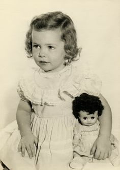 Sweet vintage photo of little girl with her doll, 1950's.