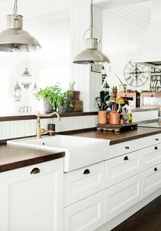 Shaker style white cabinets, copper tab and industrial lights. Loving this kitchen.