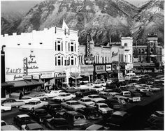 Center Street in Provo, Utah (1969) looking northeast at University Avenue and row of cars. Zale's Jewelers, House of Hallmark, Hollywood Beauty College, The Little King sandwich shop, Mitchell Jewelry, Bill Harris Music Center, Magnavox Home Entertainment Center, Anita, Thom McAn, Florsheim Shoes, Gallenkamp's Family Shoes, Shrivers, Zion's First National Bank.