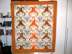 Super cute Monkey quilt...embroidered heads and appliqued tails.  body and legs/arms are pieced snail trail.