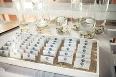 place cards in a tray of sand - beach wedding idea