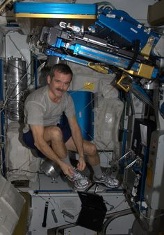 Getting ready to exercise - doing up my shoes while floating. Astronaut Chris Hadfield from the international Space Station. I like a guy who pins from space. :)