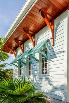 Horizontal siding, colorful Bahama shutters, a beautiful wood soffit and decorative wood brackets create an island-inspired feel at this Florida home. Tropical foliage enhances the design.