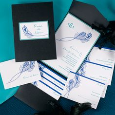 Peacock inspired wedding invitations. A bright white wedding invitation is layered on top of a teal shimmer backer. A peacock feather design adds a whimsical touch. The black shimmer pocket is perfect for adding your matching enclosures.