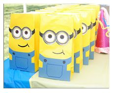 """""""yellow lunch baggies & blue heavyweight paper. I drew out a quick overall pattern to cut out for all of the bags and used the blue paper for those. I found a clear picture of the minion goggles and printed them on white cardstock. Cut those out and glued to the bag as well. With a black sharpie I drew on the minion's side smirk and free hand a overall pocket and dots for the buttons. """""""