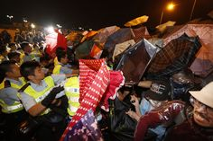 Police officers push protesters into a nearby park to clear a main road in Hong Kong's Admiralty on October 15, 2014. (AP Photo/Kin Cheung)